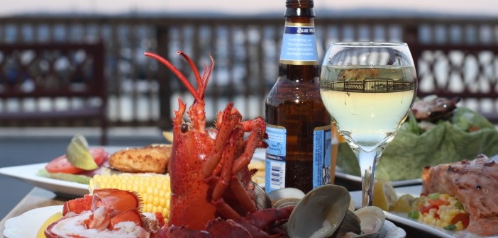 The clam bake, which includes one pound of lobster, six clams and corn on the cob, is photographed at left on a table filled with food and drinks on the marina patio at Cornetta's in Piermont on July 22, 2011. ( Xavier Mascareñas / The Journal News )