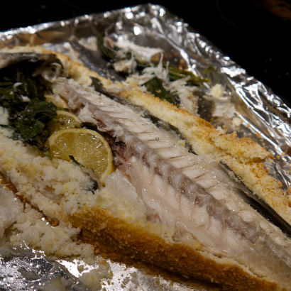 Remove the back bone of a salt crusted fish.