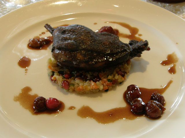 Braised duck leg with quinoa, pomegranate, vegetables and cranberry