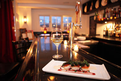The cozy bar at Plates in Larchmont, with a welcoming glass of wine and an order of sauteed sea scallops.  Tania Savayan/The Journal News